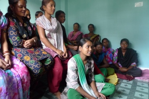 Students of the tailoring program speak to MCC staff at the BICWS Field Office.  Seated on the floor is Poonam Thakur; behind her is her teacher, Hena Gurung, herself a graduate from the program, and Hannah ??, of BICWS.
