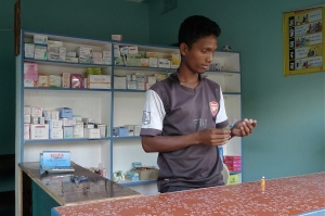 Rajis Hembrom, pharmacy student in BIC's vocational training program, loads a syringe.  Whereas many of his peers have no option but to migrate to India or other countries to seek poorly-paid work in exploitative conditions, he is able to earn a good living in his own community.