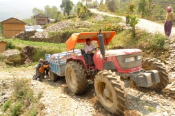 This tractor full of relief supplies needs some help making it up the rough roads of Okhaldhunga district on the way to distribute supplies in a remote earthquake affected community. MCC has supported food security and nutrition projects in Okhaldhunga district since 2010. Even at the best of times, it can be hard to reach these villages, and after the earthquake, landslides made some of the roads even worse. (MCC photo/Durga Sunchiuri)