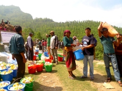 After a long, difficult journey, relief materials reach the village of Ragani, Okhaldhunga. Here, MCC Program Coordinator Durga Sunchiuri (blue shirt) helps to distribute the supplies, which include rice, lentils, salt, oil, tarps, blankets, sleeping mats, mosquito nets, and soap. (MCC photo)