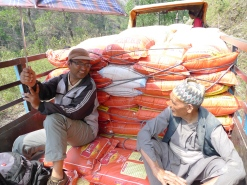 Narayan Ojha, a project coordinator for MCC's local partner SAHAS, and a local resident travel with relief items to the village of Khijifalate, Okhaldhunga. It's a 3-hour journey by tractors or motorbikes. The alternative is on foot. This tractor had to make 5 trips over 2 days to get all the relief materials from the trucks at the main road to Khijifalate village. (MCC photo/Durga Sunchiuri)