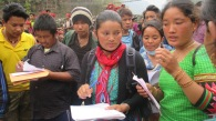 Relief distributions require careful coordination. Here, Shanti Nepal Community Health Facilitators Manju Tamang (red scarf) and Esther Tamang (behind with blue mask) cross-check the household list for distribution of relief supplies in Darkha. Shanti Nepal, with support from MCC, runs water and sanitation and community health programs in this district. (Photo courtesy of Shanti Nepal staff)