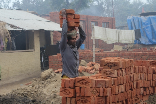 A Ramwapur man carries bricks for rebuilding his house, January 2013. MCC, with partners Janajagarun Samaj and Sansthagat Bikas Sanjal, provided materials including bricks and cement so that the homes destroyed by the fire could be rebuilt in a hazard-resistant way.